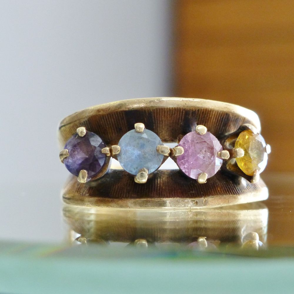 Closeup picture of a yellow gold mother's ring with an amethyst, tourmaline , blue topaz and citrine gemstones