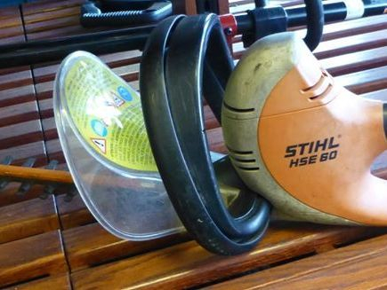 Black, orange and white stihl hedge trimmers on wooden shelf