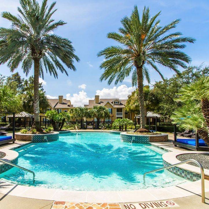 image of tropical swimming pool with palm trees, cabana beds, apartments in background