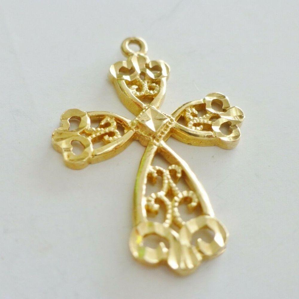 Closeup Picture of a yellow gold openwork diamond cut filigree cross pendantr