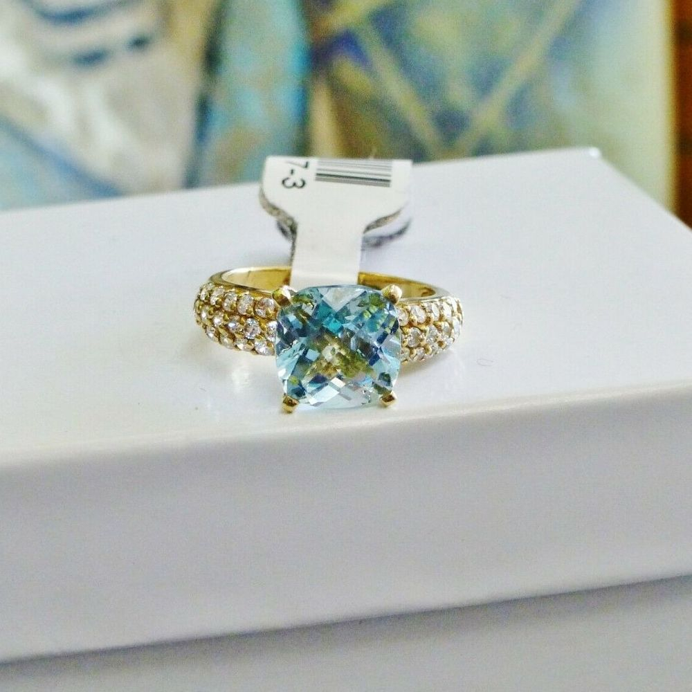 Cushion cut sky blue cz with round side accents in yellow gold ring