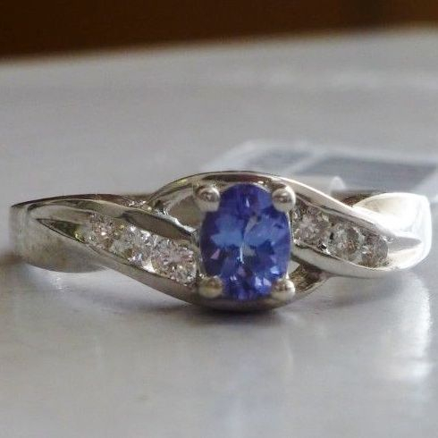 White Gold Ring With A Purple Blue Oval Tanzanite Center Stone And Round Diamond Side Accents In A Swirl Design