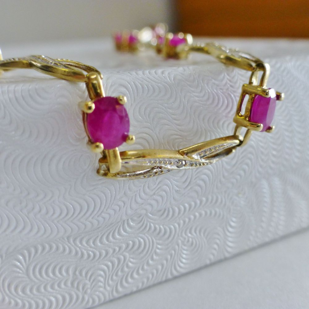 closeup picture of a two tone gold oval cut ruby diamond accent ribbon link bracelet