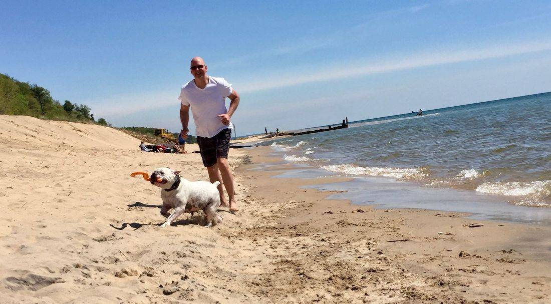 Dr. Greg Ling running on the shores of Lake Michigan with his dog Surry