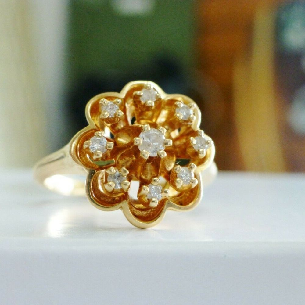 Closeup picture of a round cut diamond flower cluster cocktail ring in yellow gold