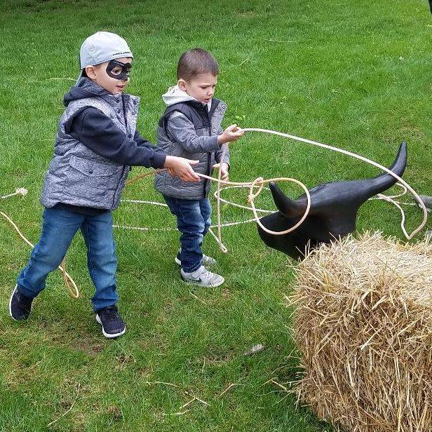 Little boys playing rope a steer with a plastic steer head stuck in a straw bale
