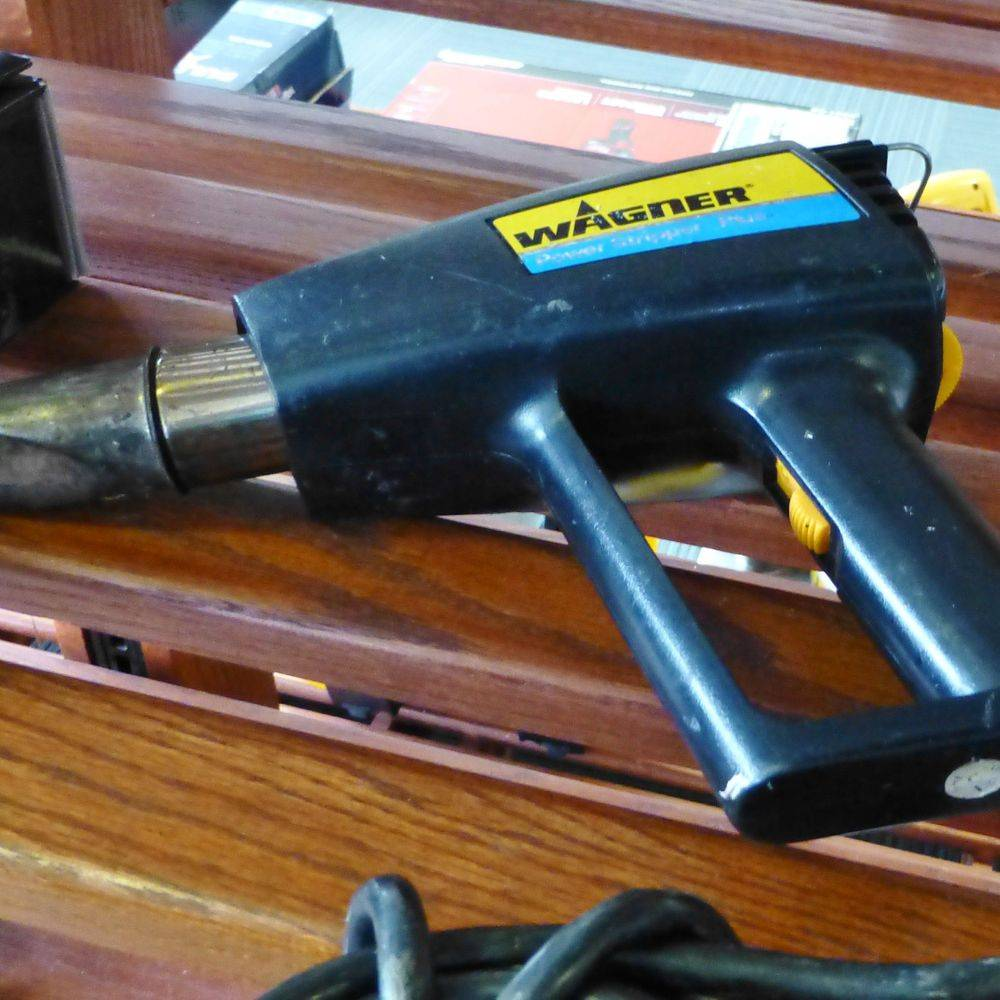 close up picture of a Wagner Stripper Heat gun laying on a wooden shelf