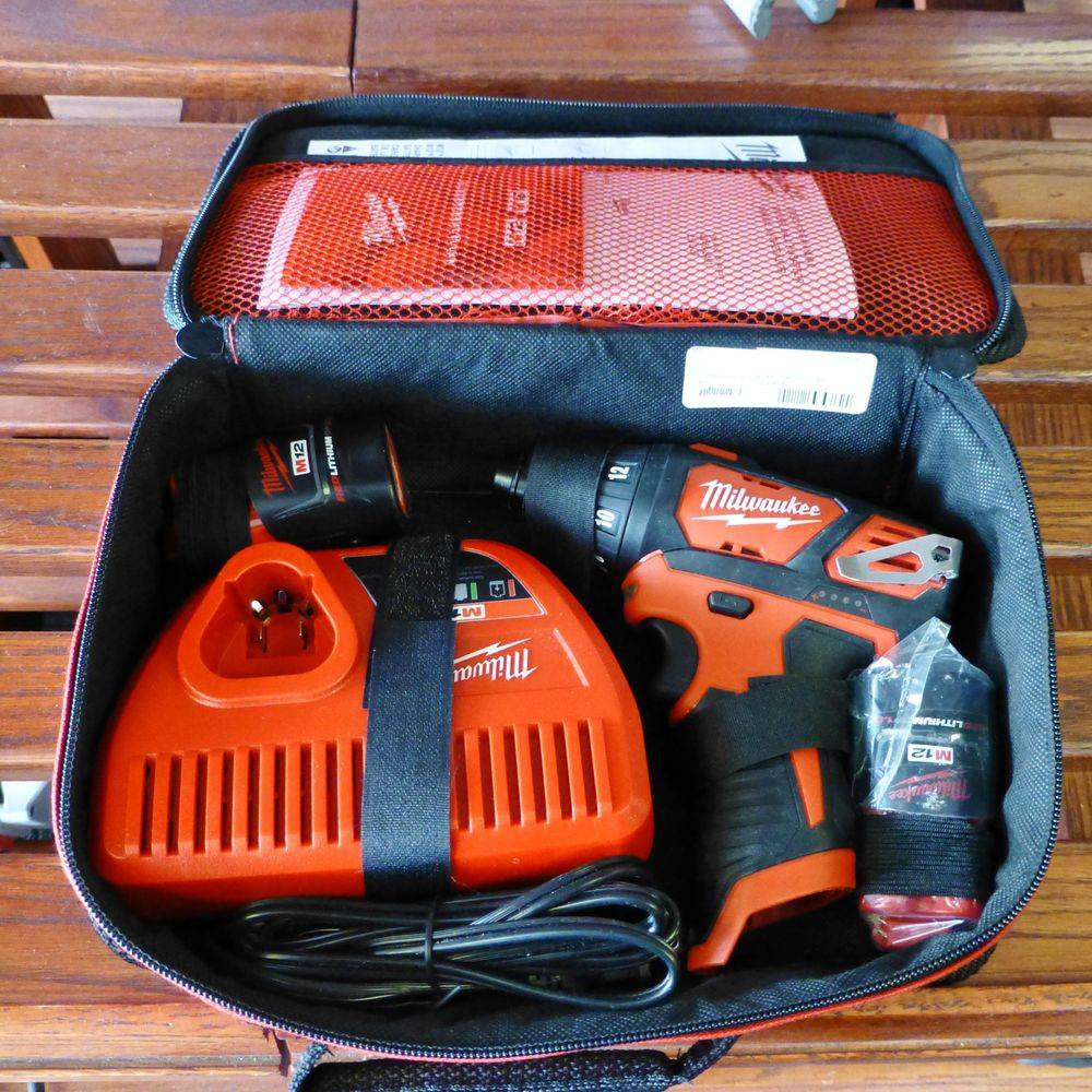 Closeup picture of milwaukee 12v screwdriver with 2 batteries, charger and softcase
