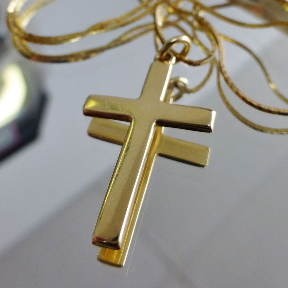 Closeup Picture of a yellow gold cross charm on a square snake link necklace