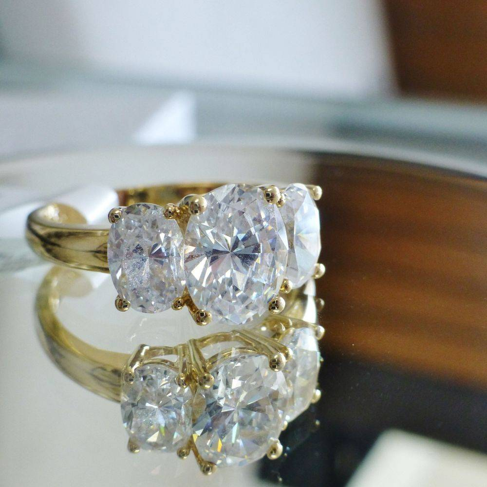close up picture of a yellow gold ring with three oval cut prong set cubic zirconia stones