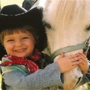 little boy in cowboy hat hugging horses head