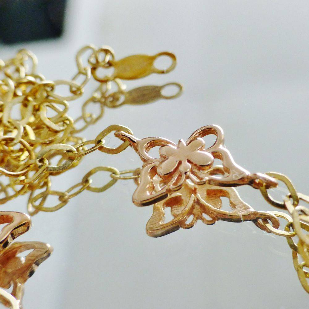 close up picture of a yellow gold oval link butterfly anklet