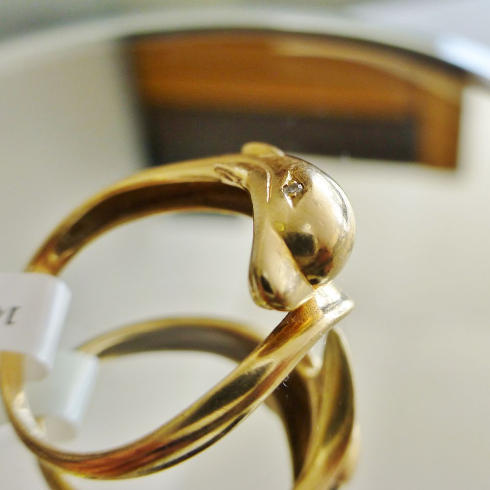 Closeup picture of a diamond eye dolphin wrap ring in yellow gold
