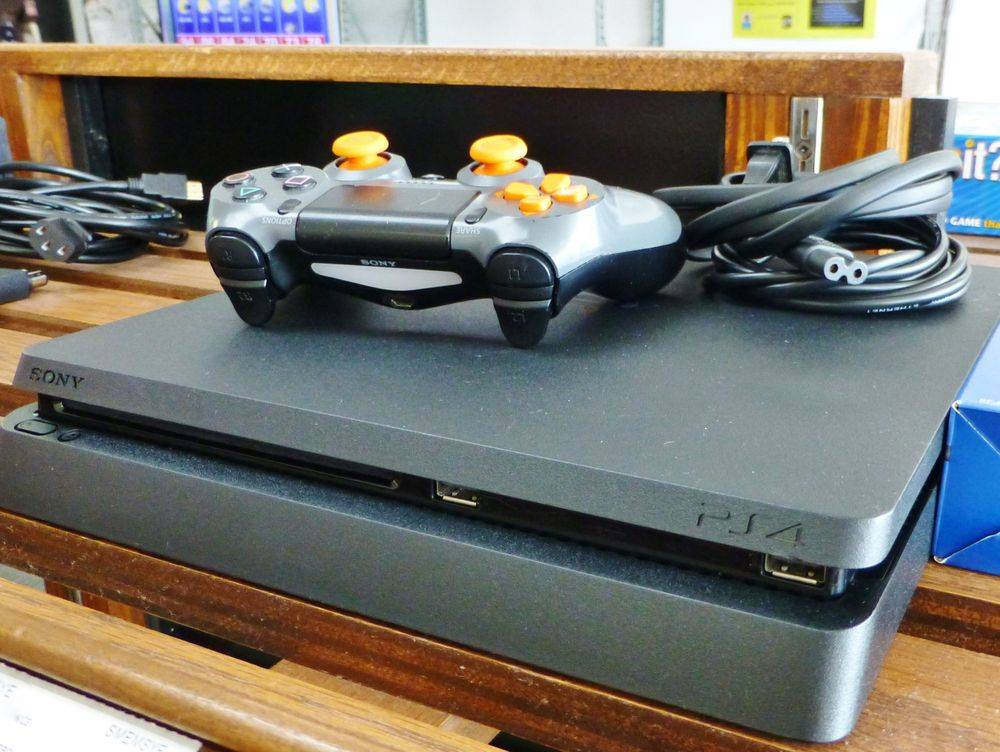 close up picture of a black Sony PlayStation 4 Slim Game Console with controller and cords