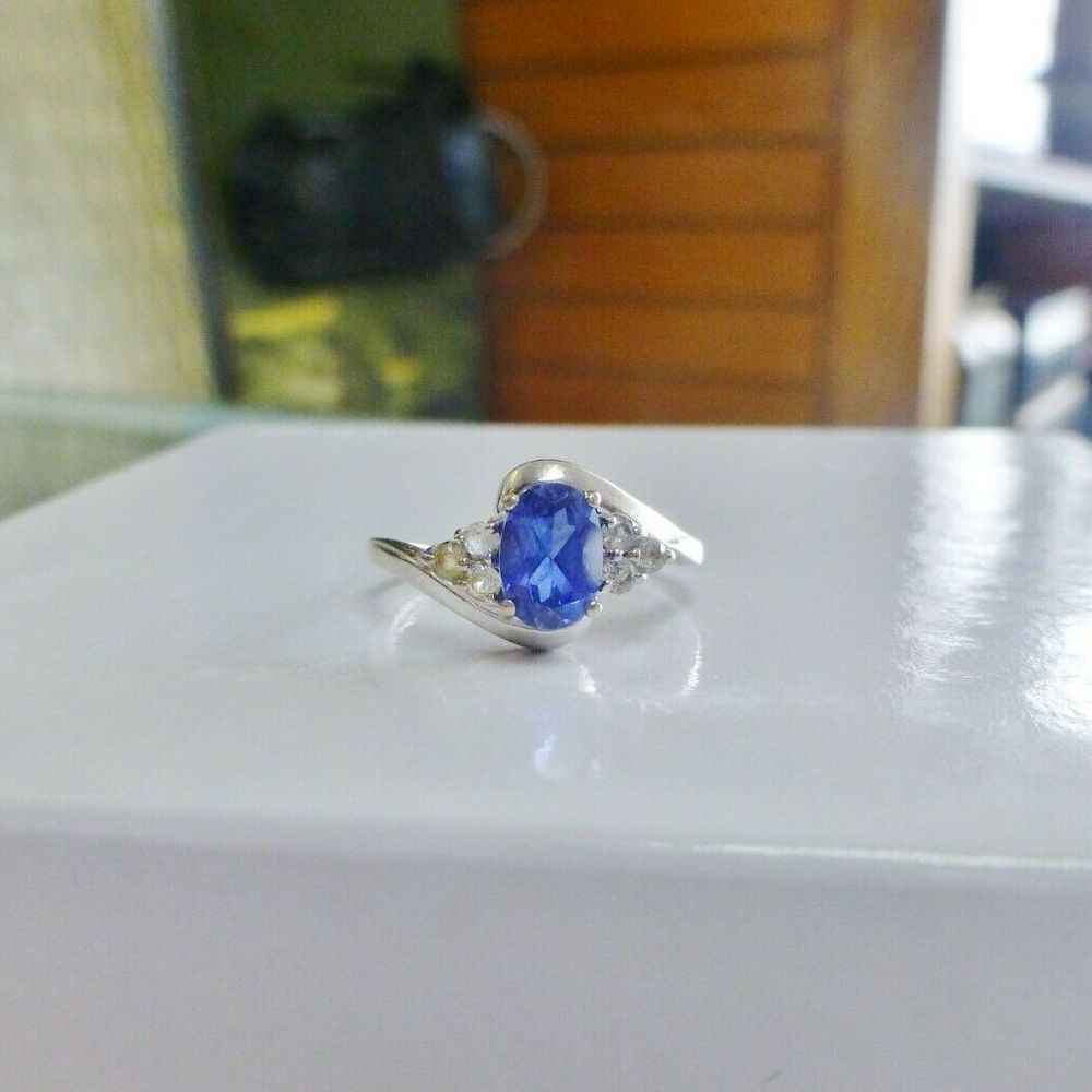 Oval Tanzanite between trio diamonds prong set in a white gold ring