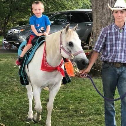 Cowboy giving a boy a pony ride on a white pony