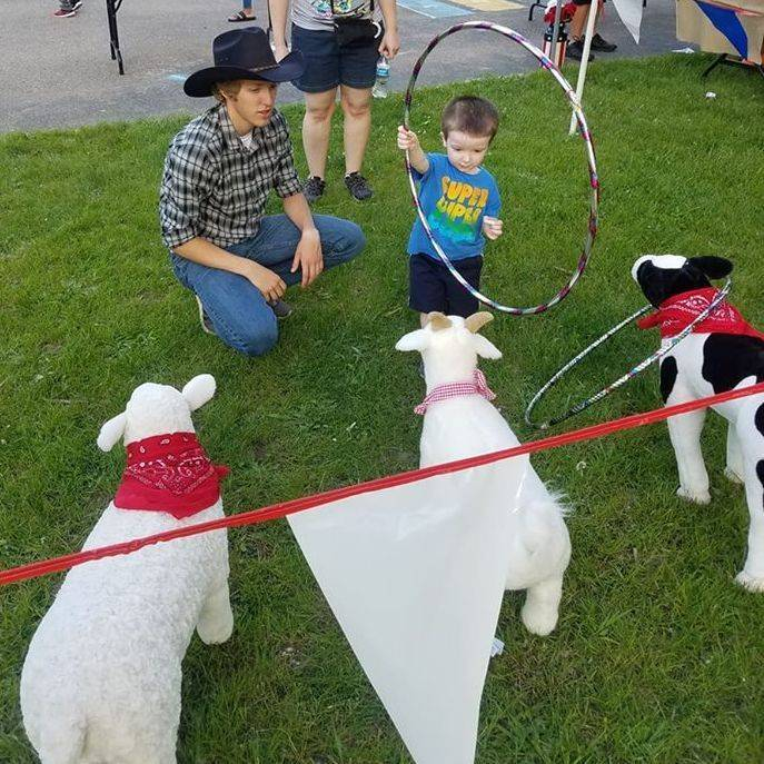 Cowboy kneeling next to little boy holding a hoop.  Playing a game of animal ring.  Get the ring over the stuffed animals head and win.