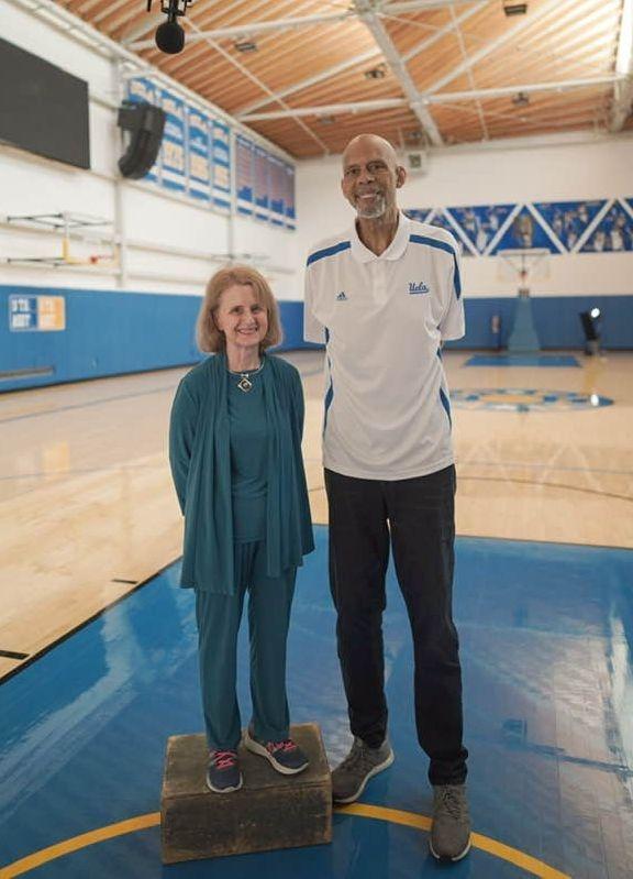 Rhoda Weiss standing next to Kareem Abdul-Jabbar, a former Lakers basketball player.