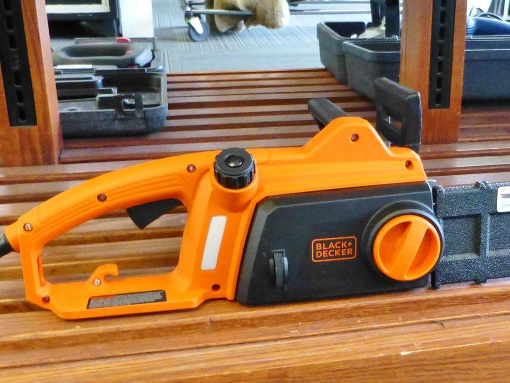 close up picture of an orange and black Black & Decker corded chainsaw sitting on a wooden shelf