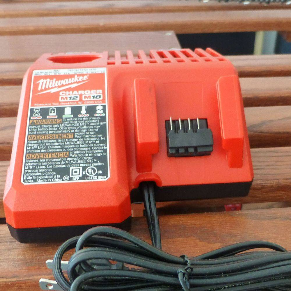 closeup picture of a red Milwaukee Battery charger on a shelf