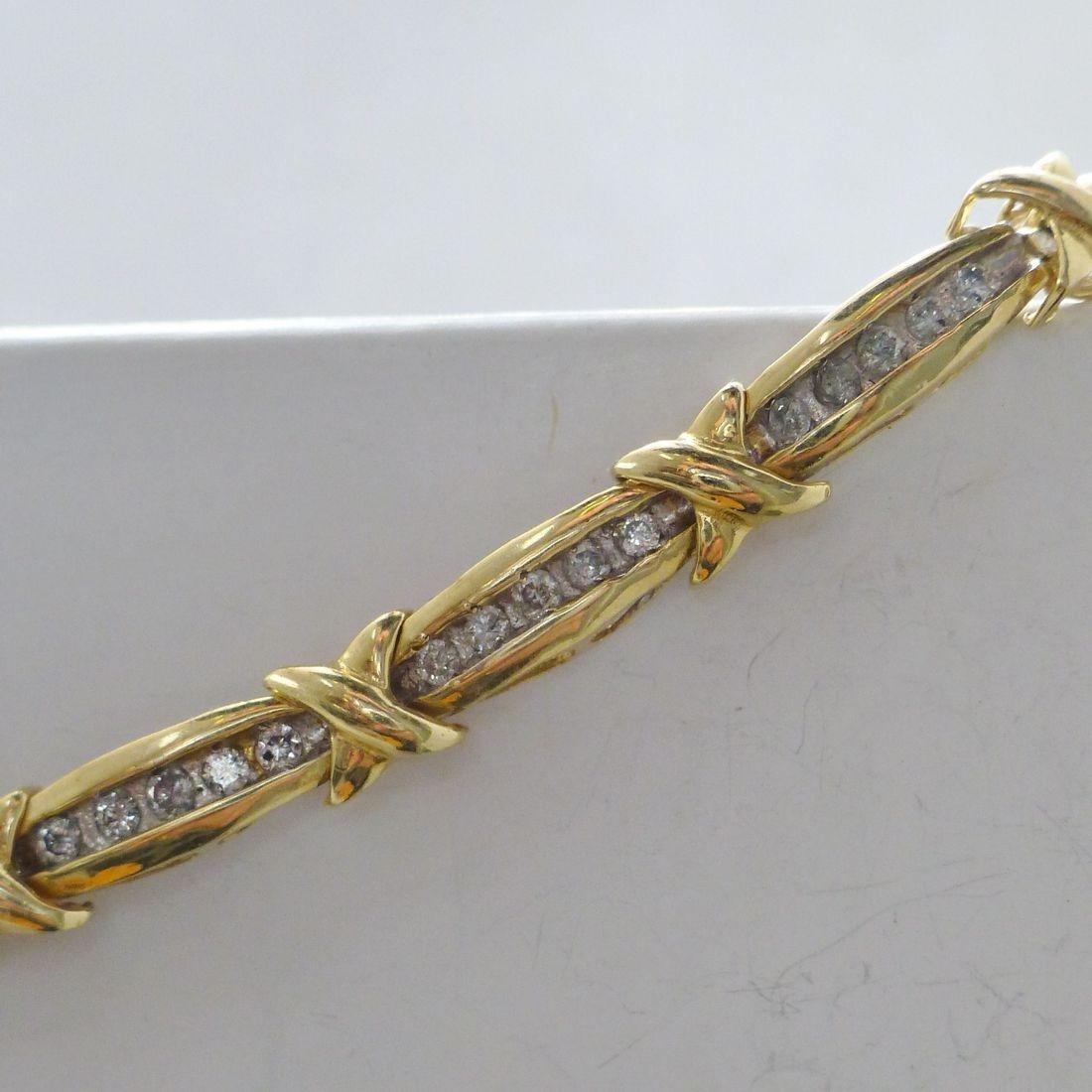 Yellow Gold Round Channel Set Diamond Tennis Bracelet Draped Across A White Box