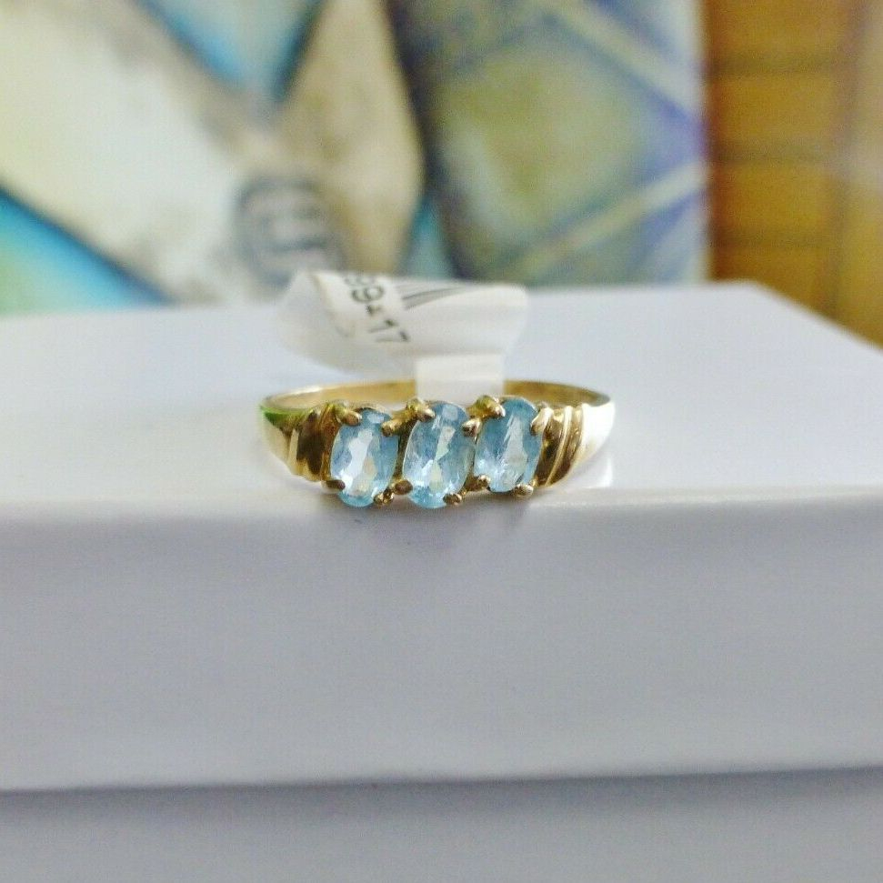 Slanted three sky blue oval cut topaz gemstones prong set in a yellow gold ring