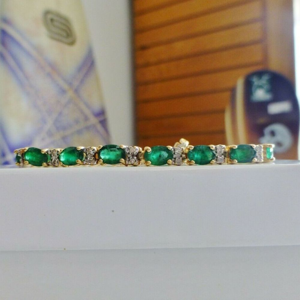 Oval green emeralds and round diamonds alternating in a yellow gold bracelet