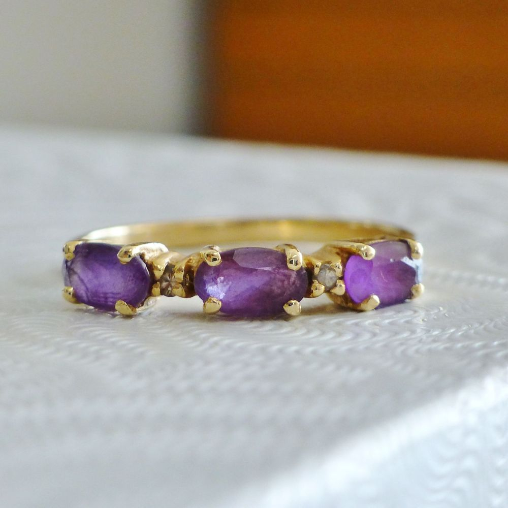 Closeup picture of yellow gold east west vintage band with three oval cut amethysts and diamond accents