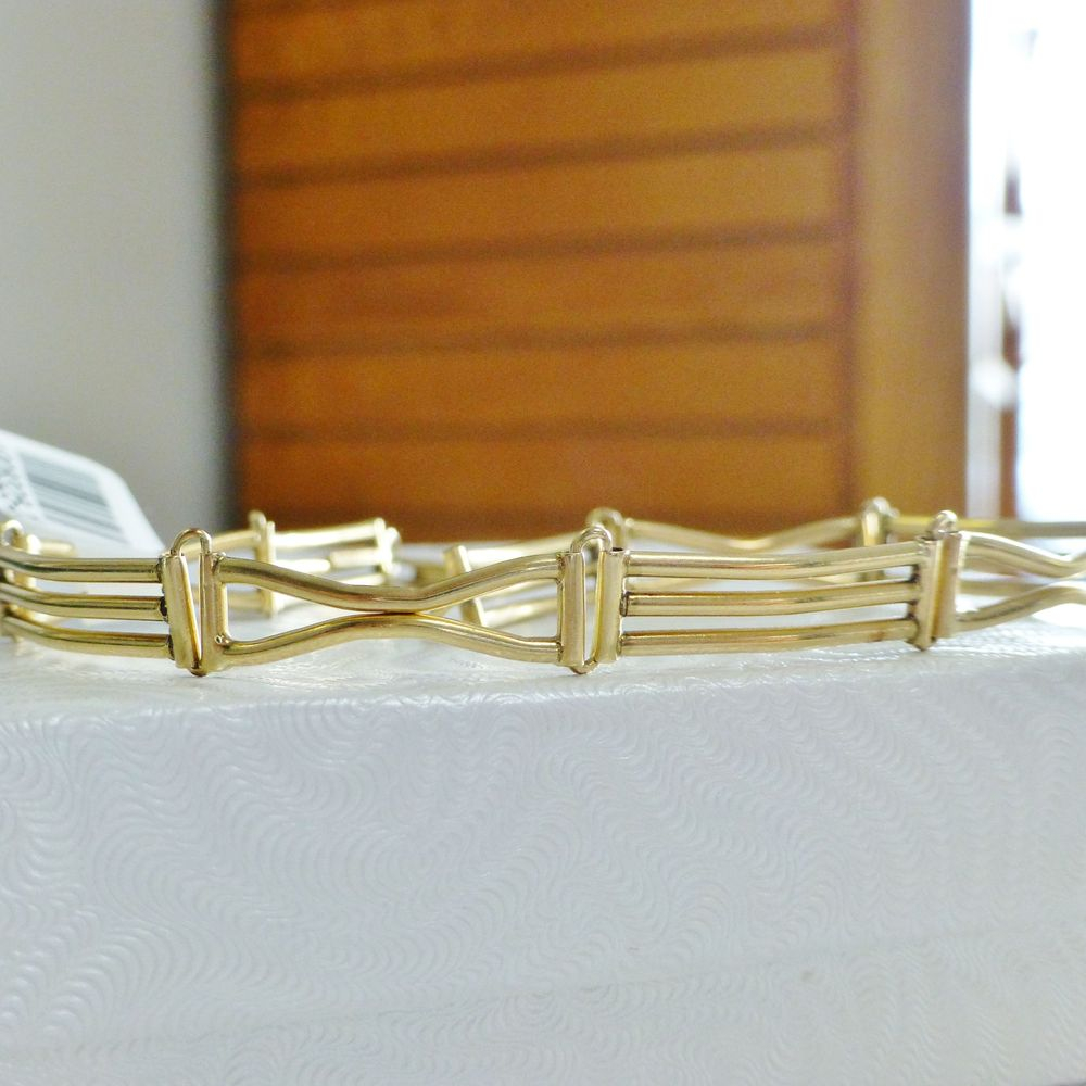 closeup picture of a yellow gold triple bar link bracelet