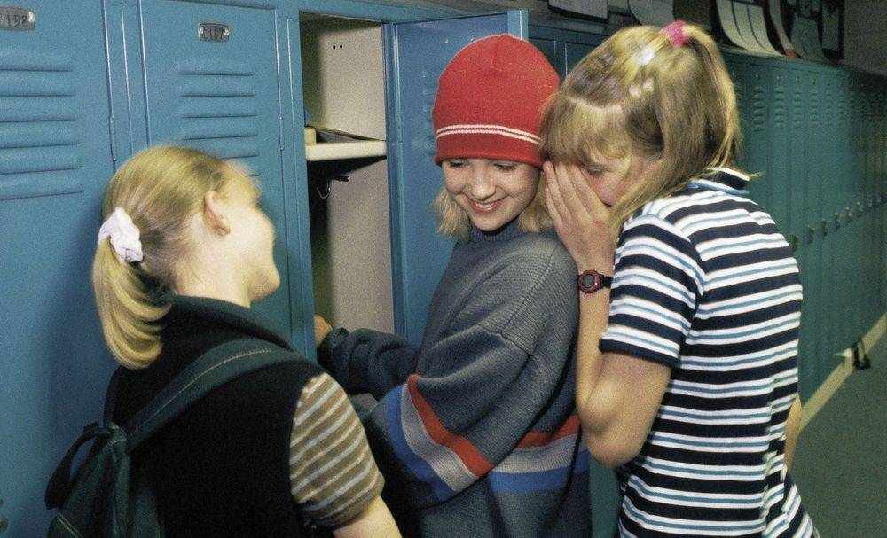 image of three adolescent girls gossiping in front of school lockers