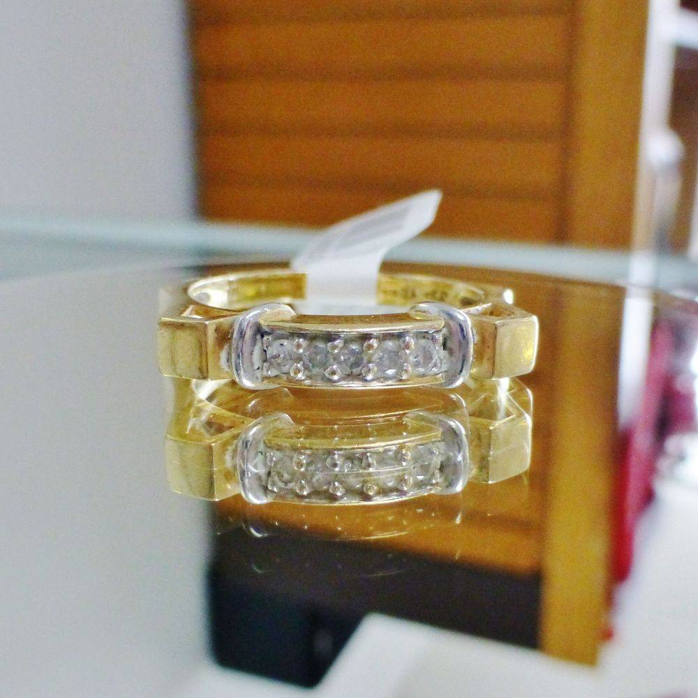 close up picture of a yellow gold vintage mens ring with five round cut diamonds prong set in white gold