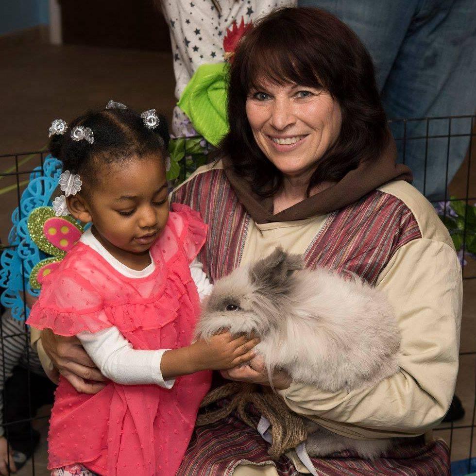 Little girl petting furry bunny