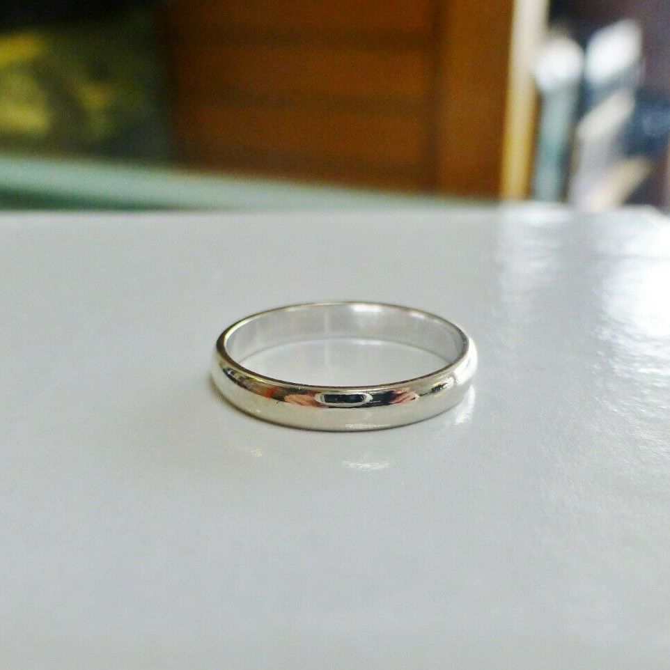 Ladies polished white gold wedding band on top of a white jewelry box