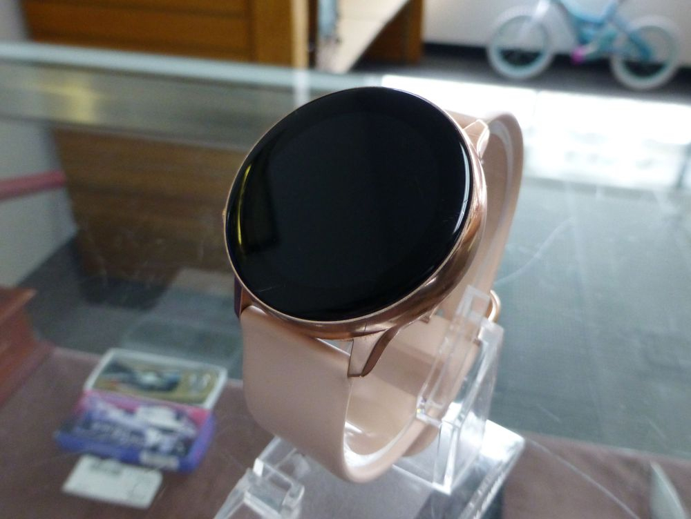 Closeup picture of a rose gold samsung galaxy active watch on a plastic stand