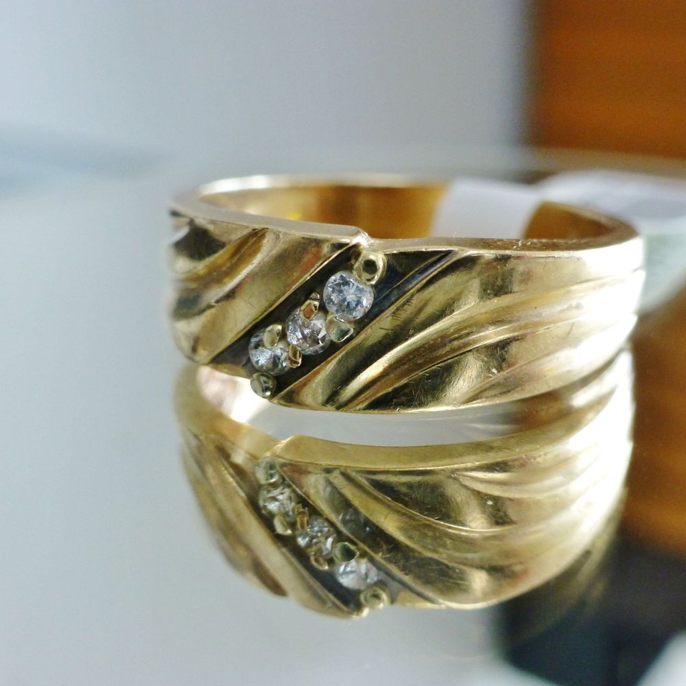 close up picture of a mens yellow gold slant wedding band with three round diamonds