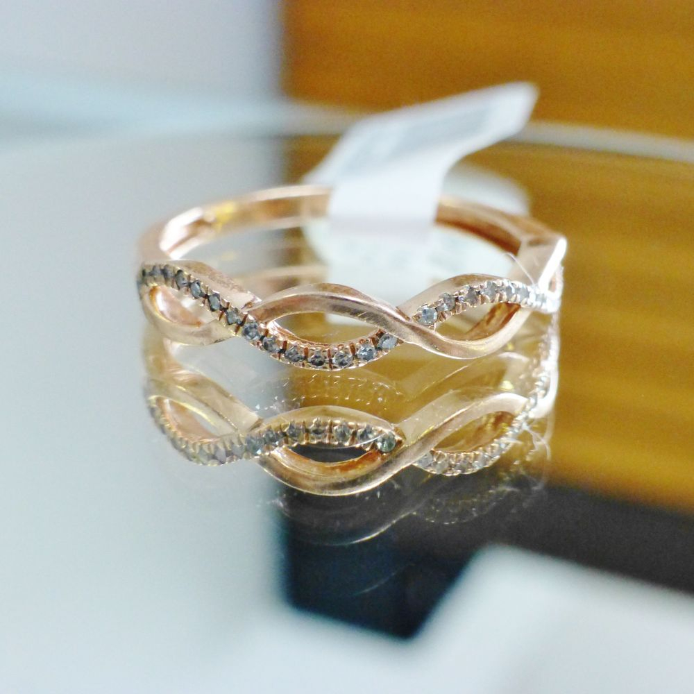 close up picture of a diamond infinity twist wedding band in rose gold