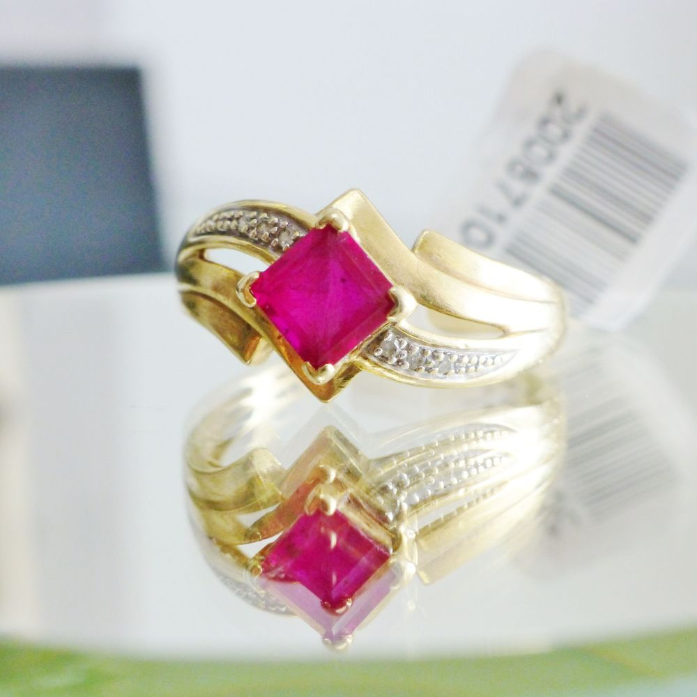 Closeup picture of a princess cut ruby prong set in a diamond accent yellow gold bypass ring