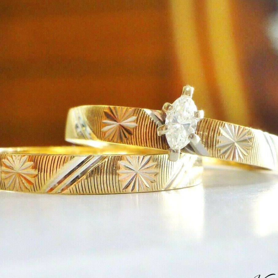 Two Tone Gold Marquise Diamond Ring Stacked on top of a matching wedding band, both with a starburst engraved design.
