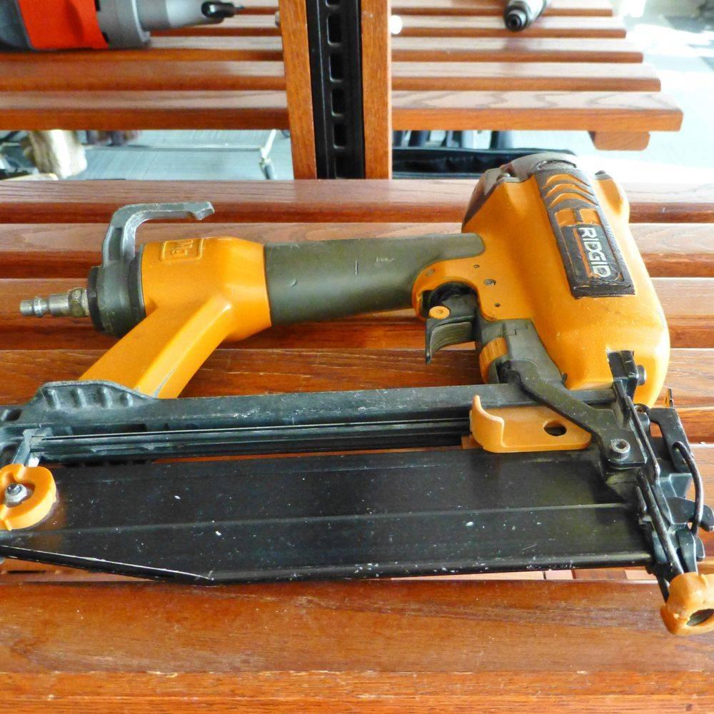 Orange ridgid pneumatic finish nail gun on a wooden shelf