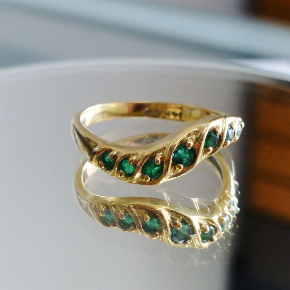 Closeup picture of a yellow gold round cut emerald seven stone wavy stacking ring