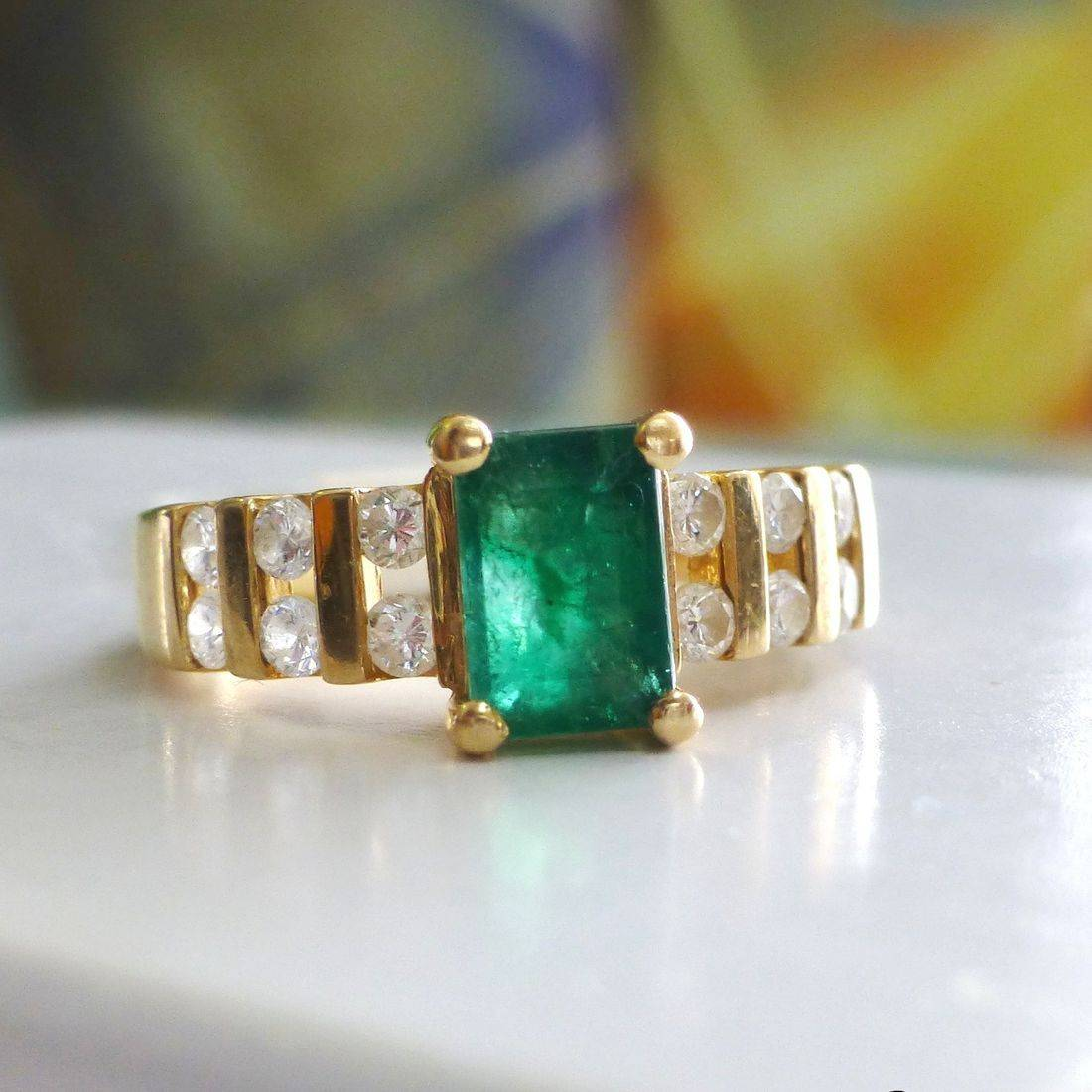 Emerald Cut Green Emerald Prong Set in The Center Of A Yellow Gold Wide Band With Three Rows Of Round Cut Diamond Pairs On The Shank