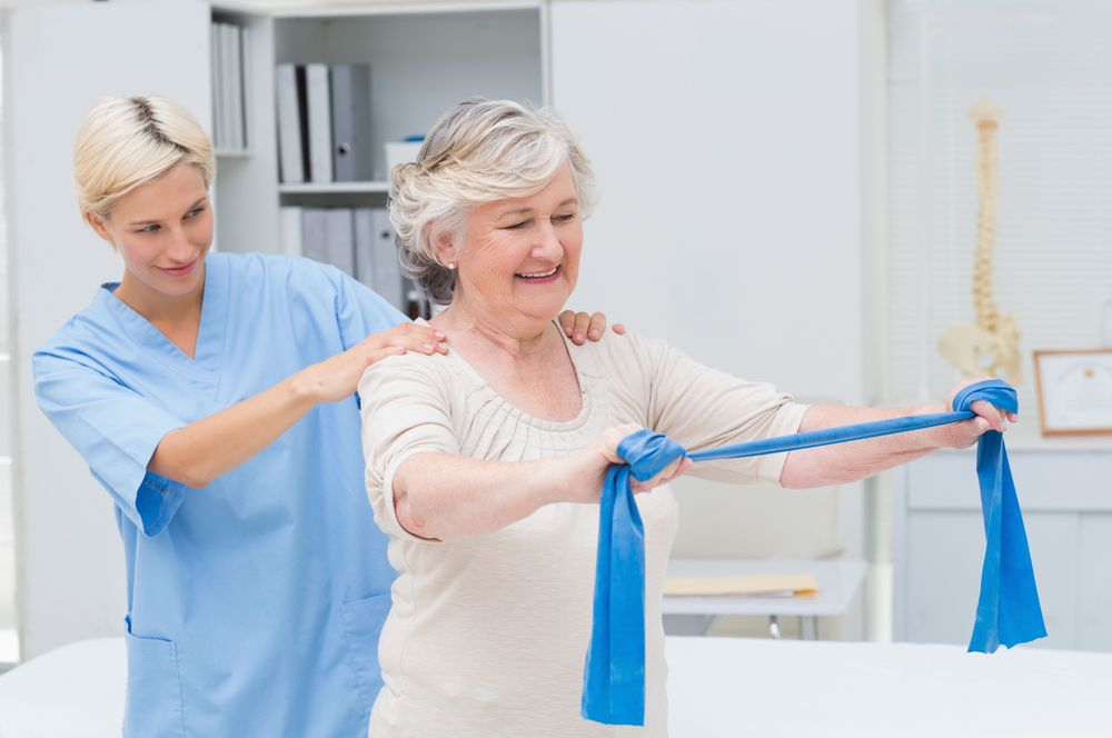Lady physiotherapist assisting patient with a theraband exercise
