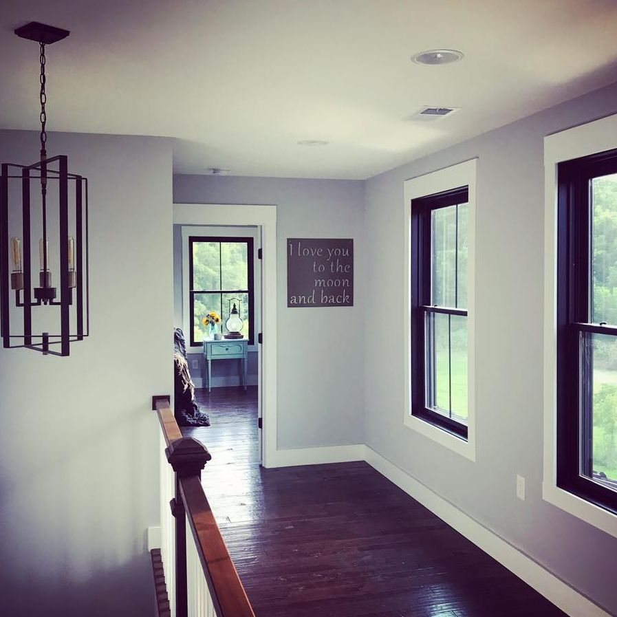 Hallway with a view, lighting, hardwood, windows, black frame windows
