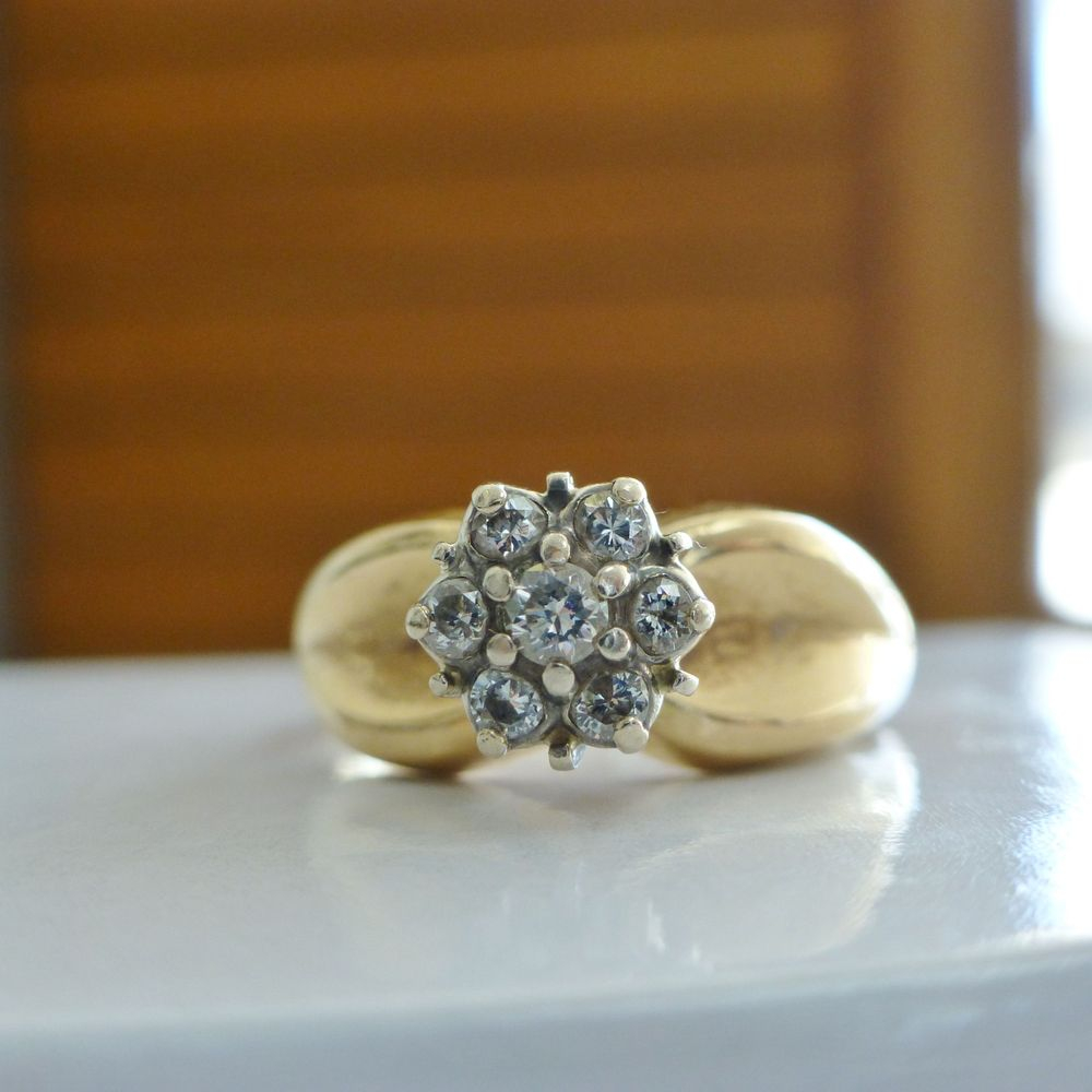 closeup picture of a round shaped diamond cluster prong set on top of a yellow gold wide band ring