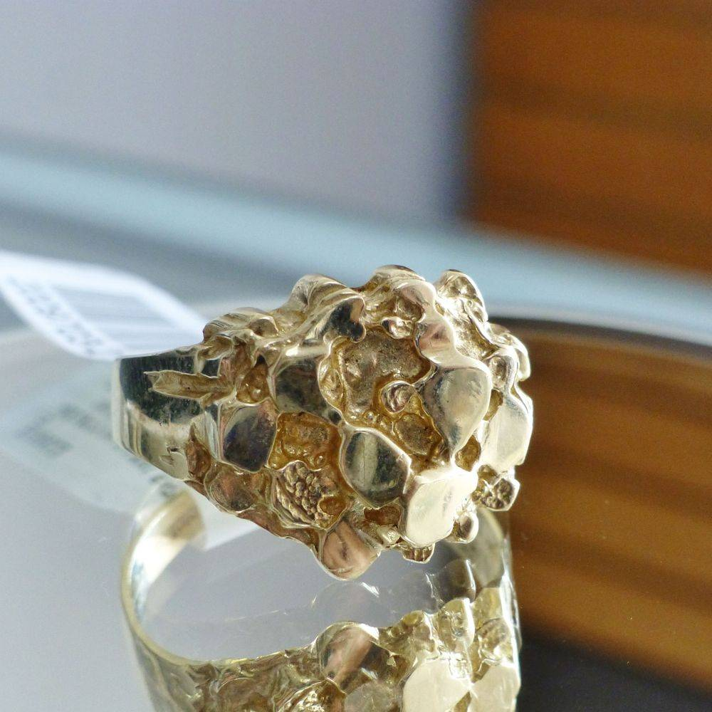 Close up picture of a yellow gold men's nugget style ring