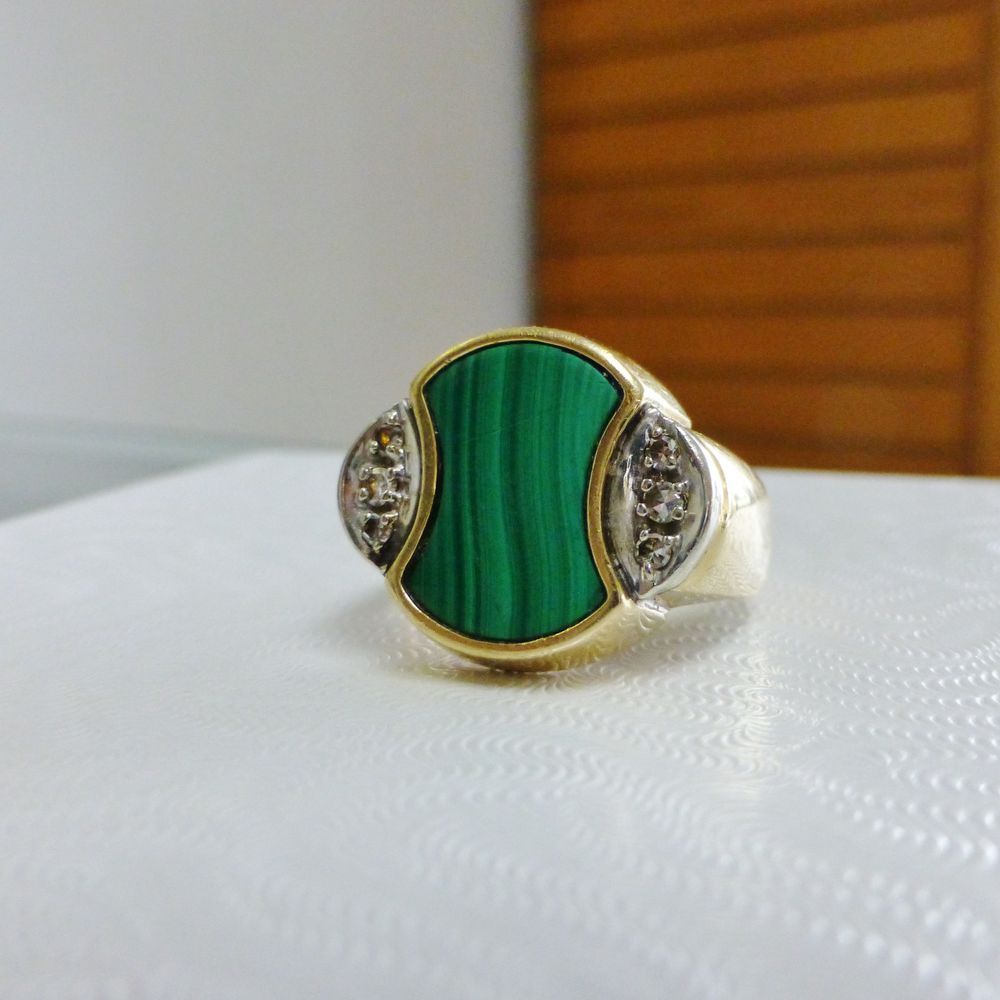 Closeup picture of a men's cocktial ring with malachite and diamond accents