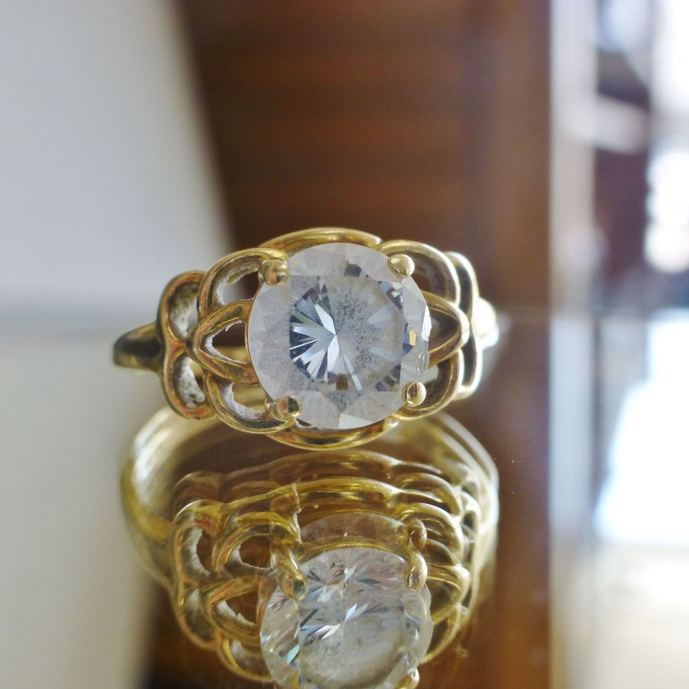 Close up picture of a yellow gold openwork ring design with a round cut cubic zirconia prong set