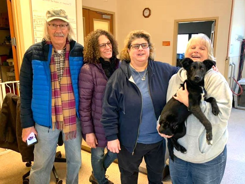 Animal Shelter volunteers and black puppy