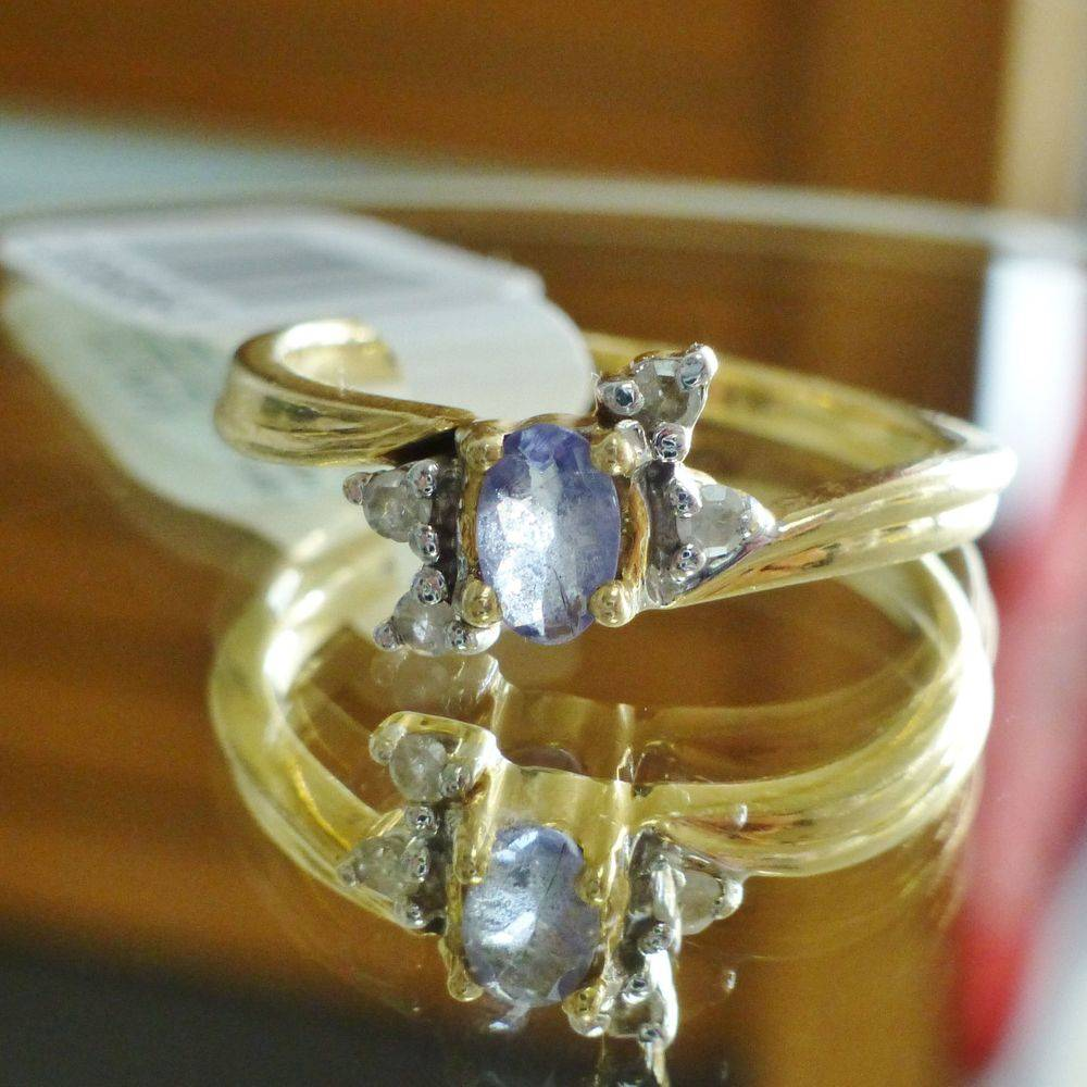 close up picture of a yellow gold ring with an oval cut tanzanite center with diamond accents