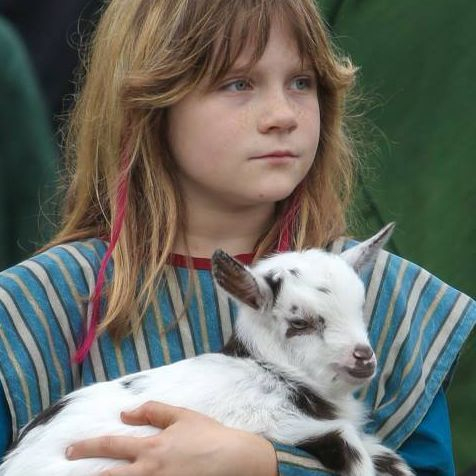 Girl dressed in costume holding a goat